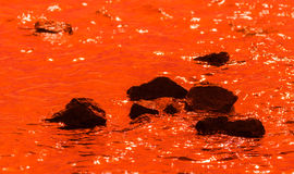 Black stones in deep orange water. Reflections of light on the water Stock Photography