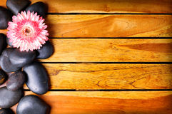 Black stones and flower on the left side on wooden. Slats. Sauna and massage concept. Horizontal composition. Top view Stock Images