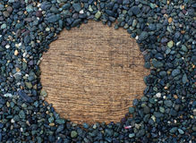 Black stones forming a circular. Pile of black stones forming a circular frame on the wood textur Stock Photos