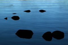 Black Stones in the Glassy Waters of Donner Lake Stock Photography