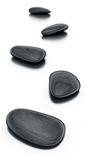 Black stones on reflective floor Royalty Free Stock Images