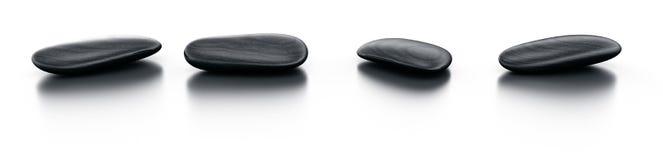 Black stones on reflective floor Stock Image