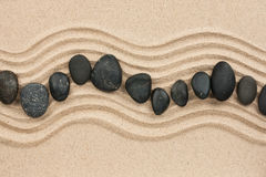 Black stones on the sand Stock Photo