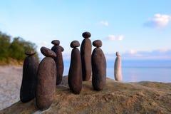 Black stones and white. White stone confront to black group on the seashore Stock Photo