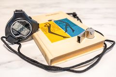 Black stop watch, training book and whistle on a marble plate royalty free stock image