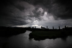 Black storm clouds over a river. And silhouette of a church Stock Photo