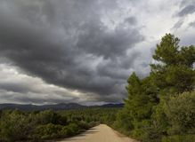 Black storm clouds on a sunny winter day in the forest and mountains on the Greek island of Evia, Greece stock photography
