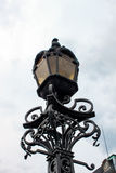 Black street lamp at day. A black street lamp in front of a cloudy sky at day Royalty Free Stock Photography