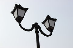 Black street lamp post against the sky. Black street lamp post against a light sky Royalty Free Stock Photo