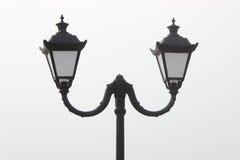 Black street lamp post against the sky. Black street lamp post against a light sky Royalty Free Stock Photos