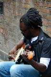 Black street musician sits against wall plays guitar London England Royalty Free Stock Image