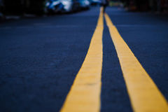 The black street with yellow line, selective focus, blurred back. Black street with yellow line, selective focus, blurred background royalty free stock photo