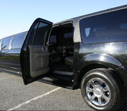 Black stretch limo with door open. Black stretch limousine with rear door open beckoning guests Royalty Free Stock Photography