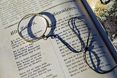 Black String on Top of an Open Book during Daytime Stock Photos
