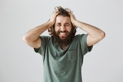 Black stripe in life begun. Indoor shot of troubled devastated eastern man with beard holding hans on head and grimacing. From pressure and miserable emotions stock photography