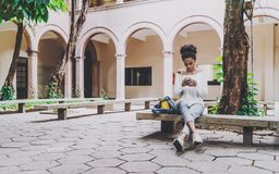 Black student girl in the university yard with the cellphone. Young cute Brazilian undergraduate girl is sitting in the courtyard of her univercity on the Stock Image