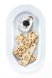 Black sturgeon caviar and matzah on plate, view from above. With Stock Photo