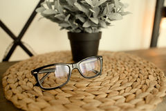 Black stylish glasses on Wicker stand in loft interior in scandinavian style Royalty Free Stock Photos