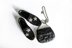 Black suede shoes with a rhinestone star decoration and a black clutch on a chain with stars on a white background stock photography