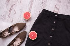 Black suede skirt, brown suede shoes, cut grapefruit halves. Wooden background. Fashion concept. top view Stock Photos