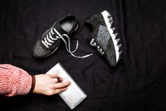 Black suede sneakers decorated with silver sequins and a female hand with a silver purse on a black woven background royalty free stock photo