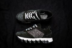 Black suede sneakers decorated with silver sequins on a black woven background royalty free stock images
