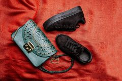 Black suede sneakers and a turquoise bag with carved patterns and metal studs on a red woven background stock images