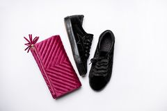 Black suede sneakers and velvet purple clutch over a white background stock photography