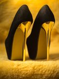 Black suede womens shoes with high gold heels. Black suede womens shoes with high golden heels stock images