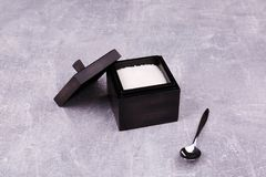 A black sugar bowl with a spoon stock photography
