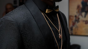Black Suit With Bowtie. Textured Black Suit with black n gold bowtie, draped in gold chains and ruby stones Stock Image
