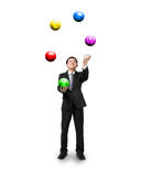 Black suit businessman juggling currency symbol balls. Isolated on white Stock Photography