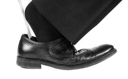 Black suit, socks into black leather shoe with shoehorn Royalty Free Stock Photo