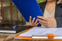 Black suit woman hand wearing ring holding folder while working. Black suit woman hand wearing ring holding document while working stock images