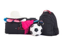 Black suitcase with clothing, backpack and ball isolated on whit Stock Photography