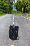 Black suitcase on a country forest road Royalty Free Stock Image