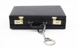 Black suitcase from pinned handcuffs Stock Images