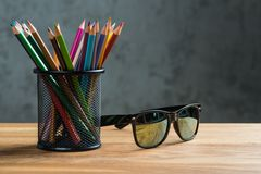 Black sun glasses with bunch of color pencils in a stand Royalty Free Stock Images