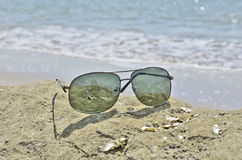 Black sun glasses with rock. Black sun glasses on the rock beside the sea Royalty Free Stock Photo
