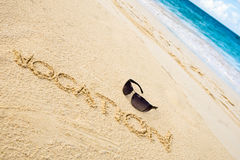 Black sun glasses on white sand beach Royalty Free Stock Image