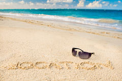Black sun glasses on white sand beach Stock Image