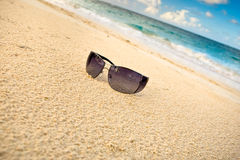 Black sun glasses on white sand beach near sea Stock Photography