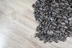 Black sunflower seeds lie on a wooden background in the right side of the frame Royalty Free Stock Images