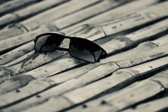 Black sunglass kept on a bamboo surface stock photo. The beautiful black sunglass kept on a bamboo made surface stock photograph stock photo