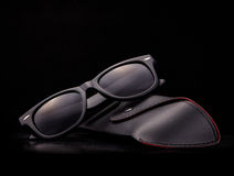 Black sunglasses with case on black background. Stock Images