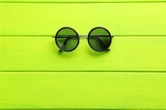 Black sunglasses. On a green wooden table Stock Images