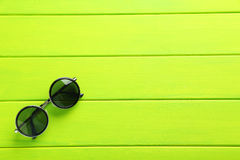 Black sunglasses. On a green wooden table Stock Image