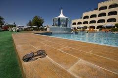 Black sunglasses near pool. Wide angle shot of black sunglasses near pool Royalty Free Stock Images
