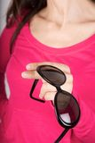 Black sunglasses on pink sweater background Stock Image