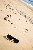 Black sunglasses on the sand. At sunny day Stock Image